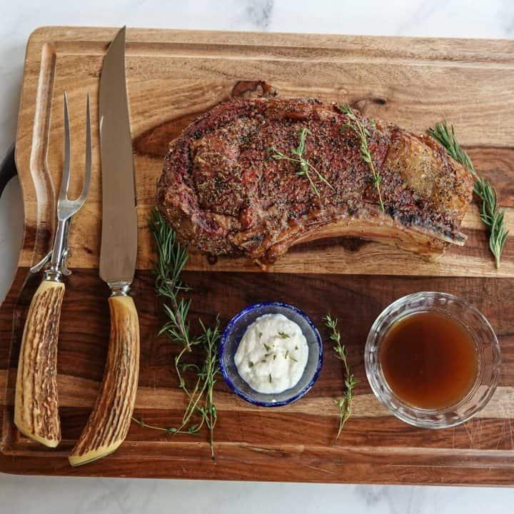 rib roast on cutting board with knife, fork, au jus, and horseradish sauce