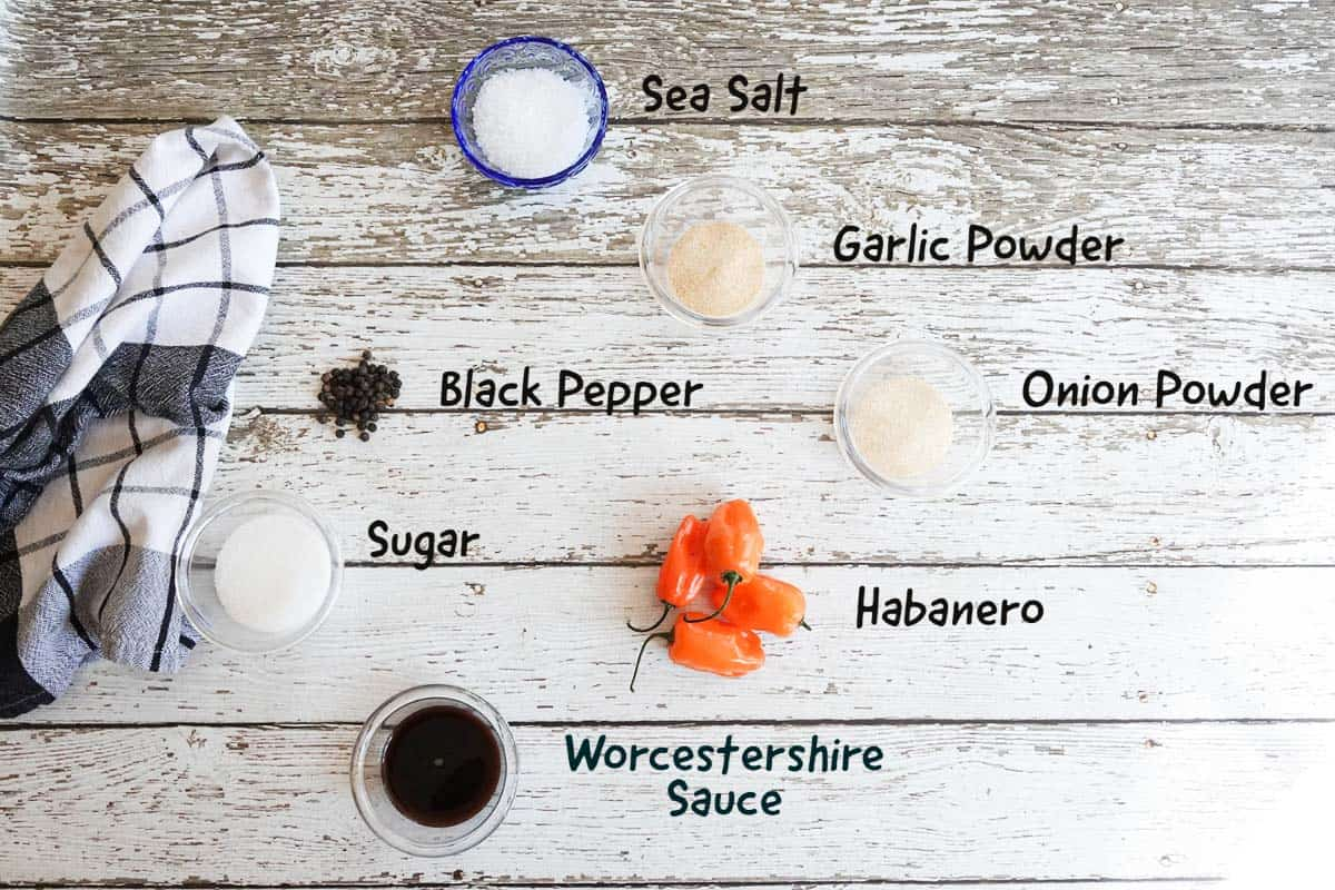 Ingredients with labels on white wooden background