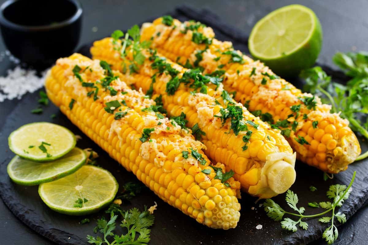 corn with cheese, cilantro and limes on black board