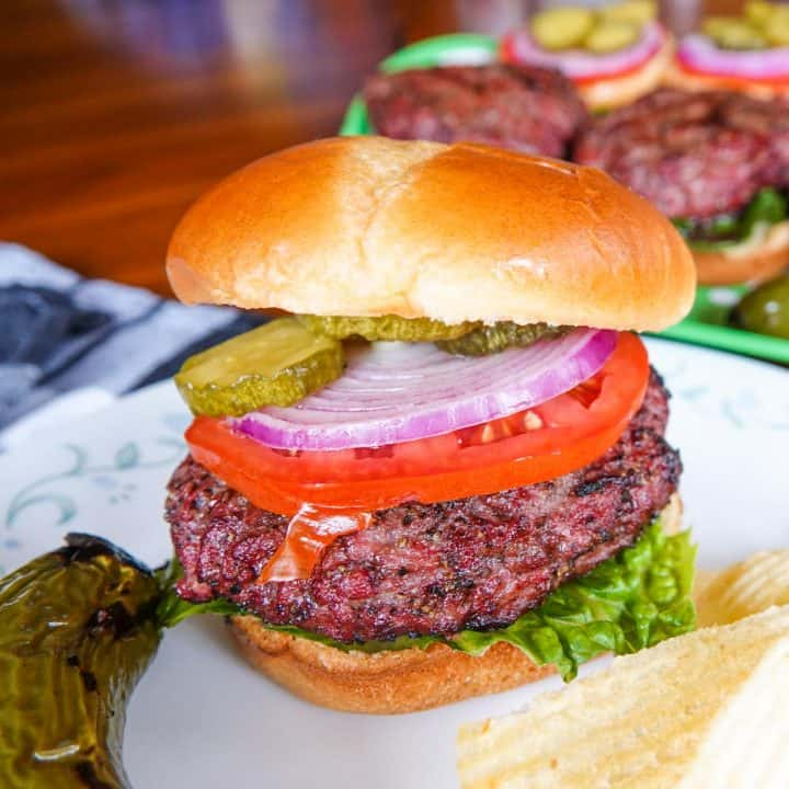 Hamburger with tomato, pickles, onions on plate with burgers in background