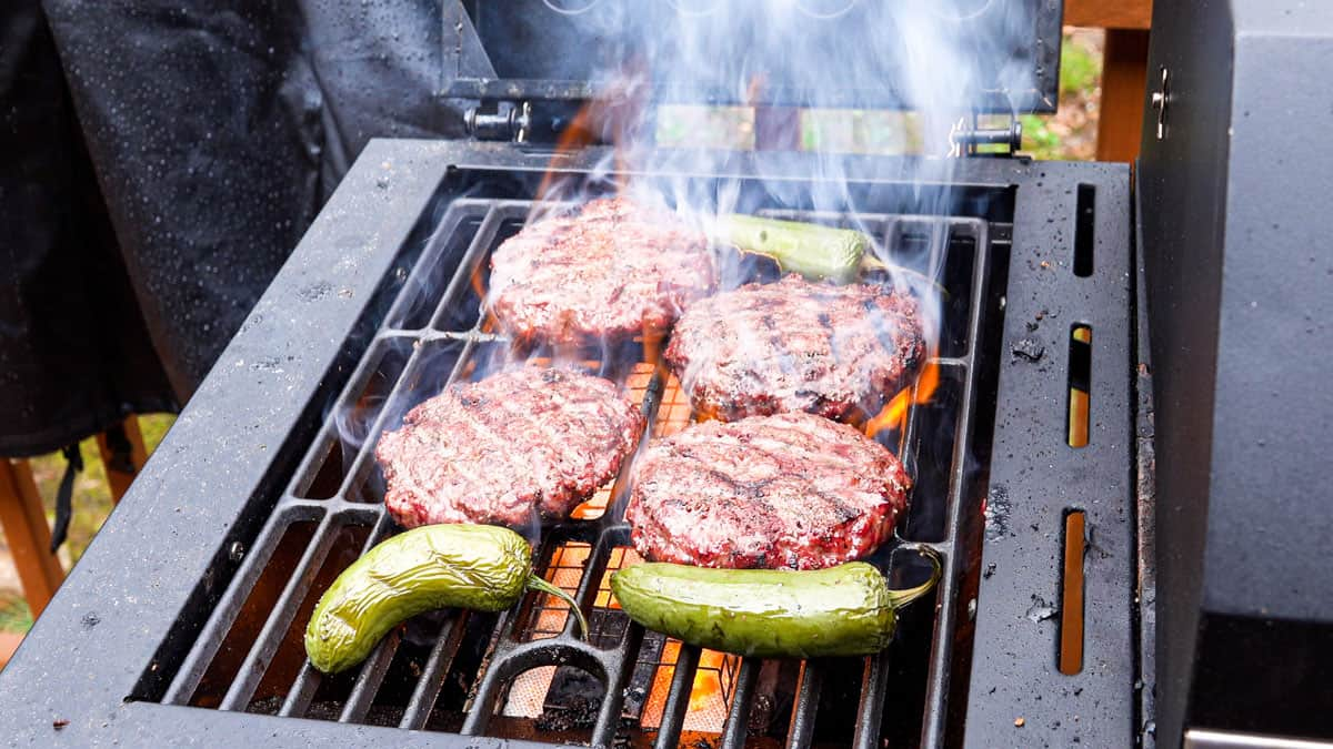 Hamburgers searing on grill with jalapenos