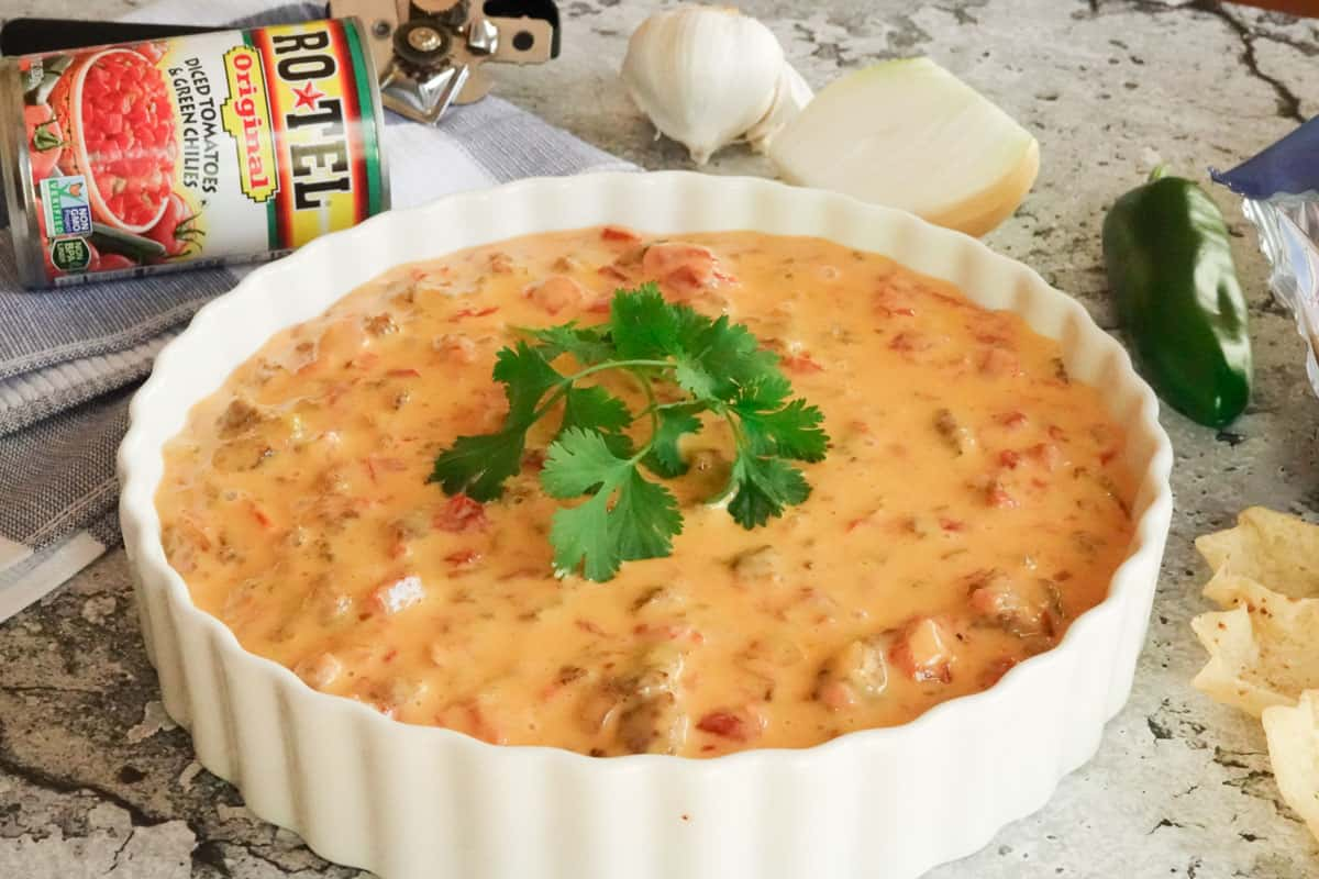 Queso dip in white dish with can of tomatoes and chips and jalapeno