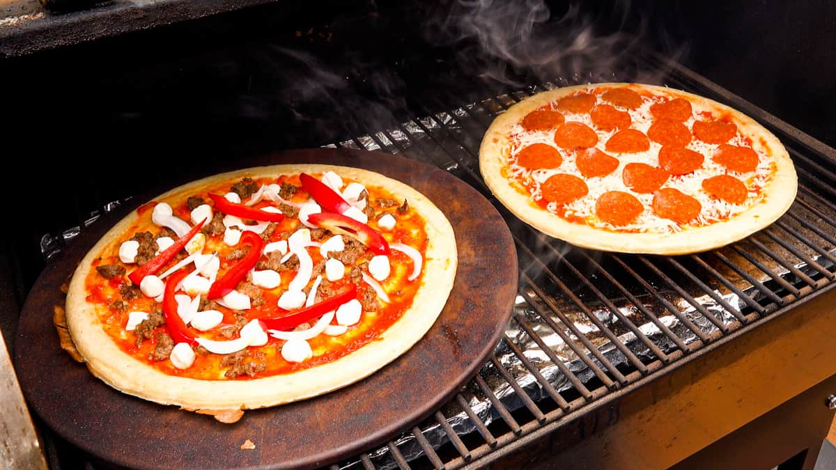 two pizzas on smoker rack cooking