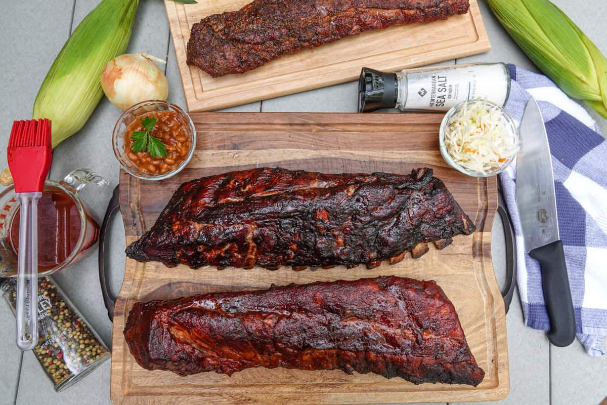 Smoked ribs on cutting boards with corn, bbq sauce, and coleslaw