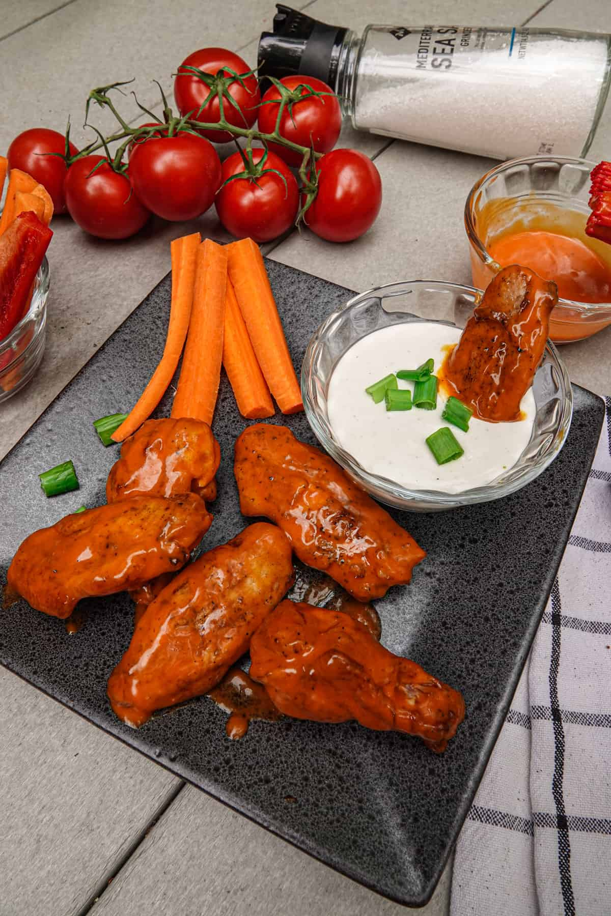 Chicken wings on plate with ranch sauce, carrots, and tomatoes