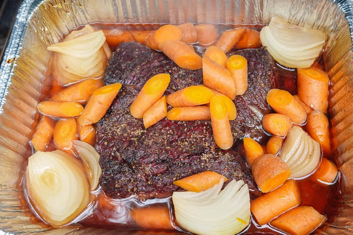 chuck roast in aluminum pan with beef stock, carrots, and onions