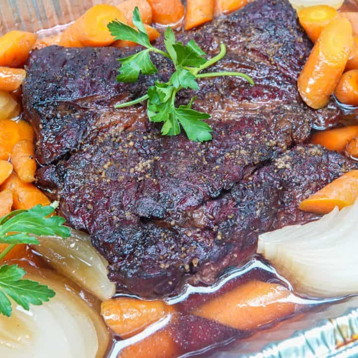 chuck roast in pan with beef broth, carrots, and onions garnished with parsley