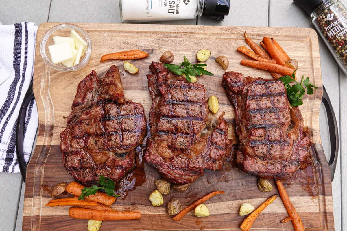 Three ribeye steaks cooked on cutting board with carrots and potatoes