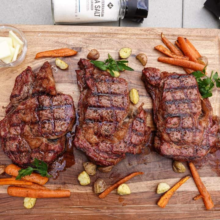 Three smoked steaks on cutting board with carrots and potatoes