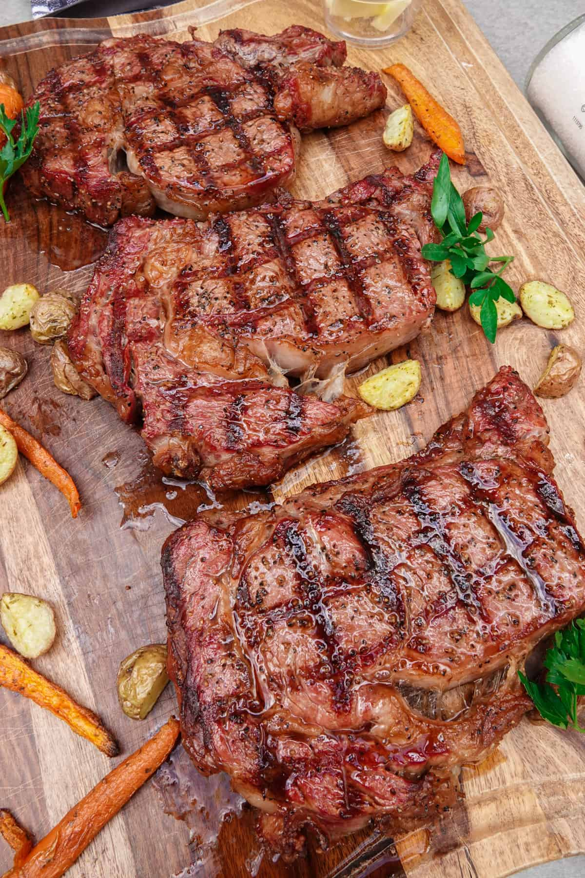 Three cooked ribeye steaks cooked on cutting board