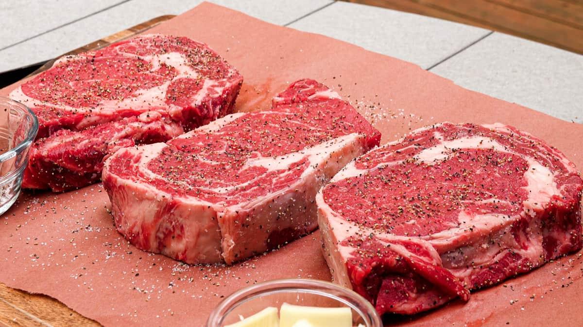 three ribeye steaks seasoned with salt and pepper