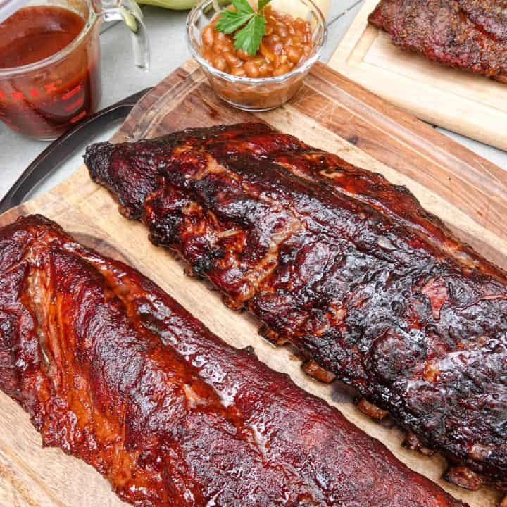 Two racks of ribs on cutting board with baked beans