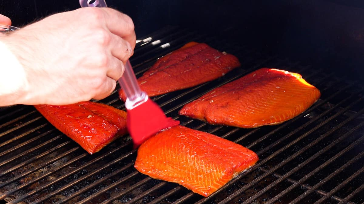 smoked salmon on smoker being basted with glaze