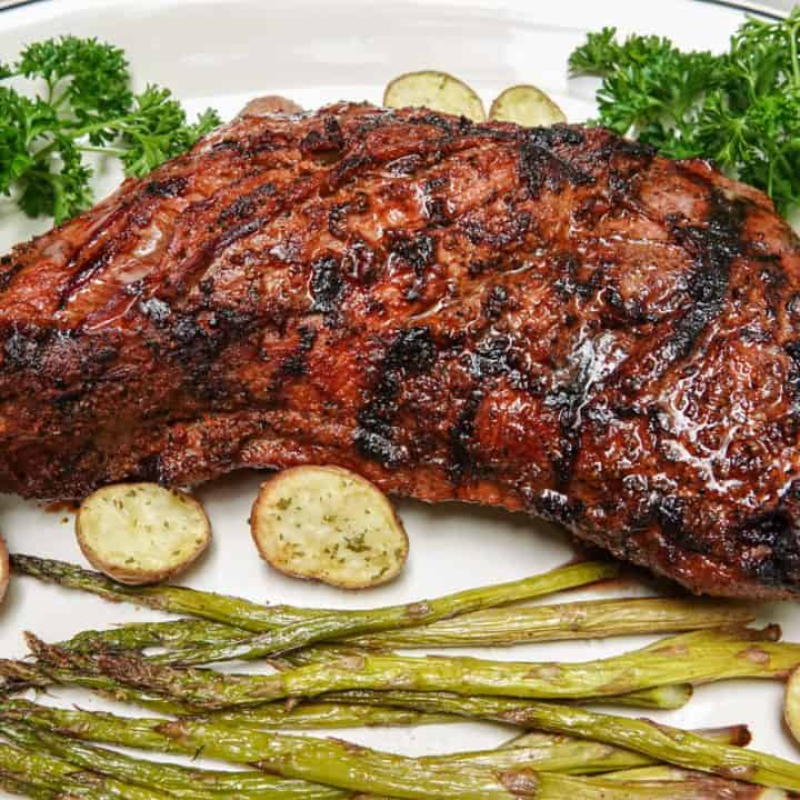 Tri tip steak on plate with potatoes and asparagus