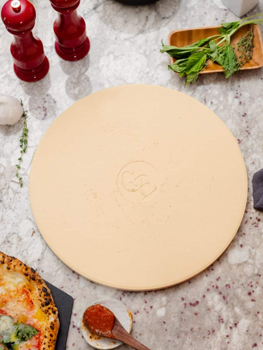Pizza stone with salt and pepper shaker and marinara sauce on spoon